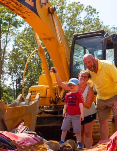 Family cheer over crushed car with excavator behind them