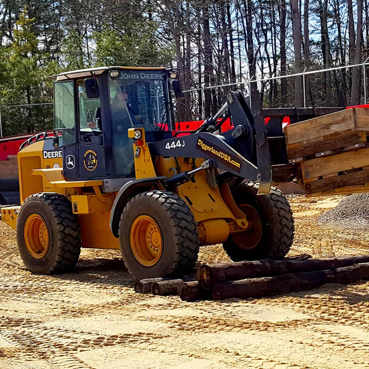Wheel loader climbs logs with pallets on forks