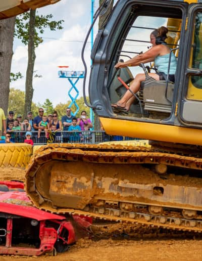 Woman drives over crushed car in excavator